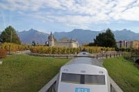 An Amtrak miniature train passing a small Chateau d'Aigle Castle in the Swiss Vapeur Parc