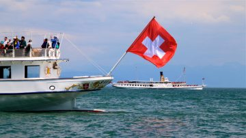 Swiss flag waving from a Lake Geneva paddle steamboat